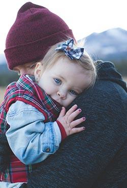 Enfant dans les bras d'un parent